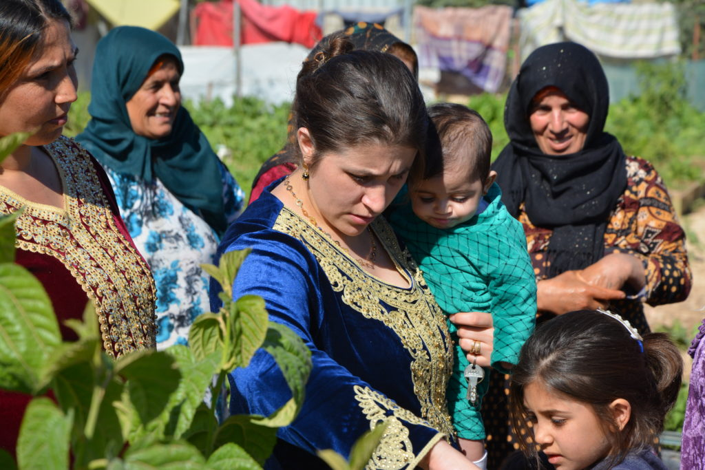 Group of female community gardeners and children in Azadi Community Garden, Domiz 1 camp, Kurdistan