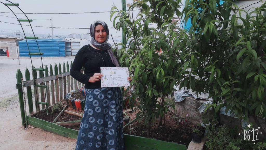 Ibrahim Jarado, winner of the 2019 Lemon Tree Trust gardening competitions in Khanki camp, holding her certificate.