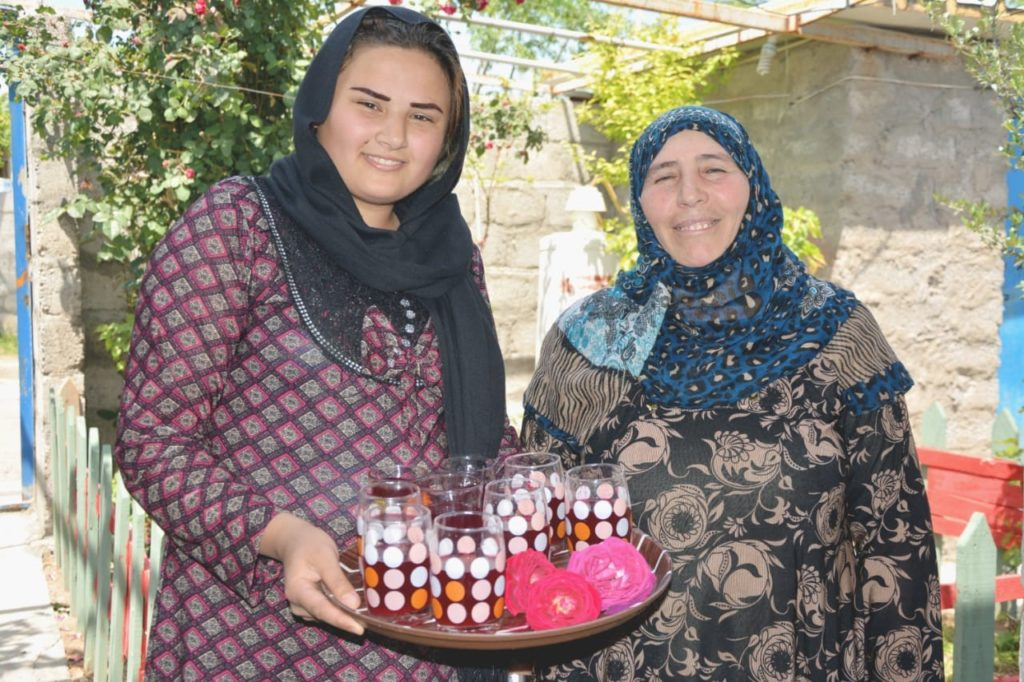Khadeja Tahr Omer with her daughter holding a tray of glasses filled with rose water