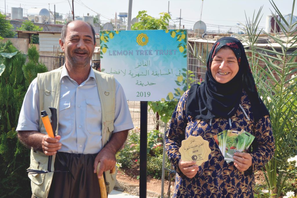 Muhammed Hssen and Zainab Abdullah holding their Garden of the Month plaque and seed packet prize