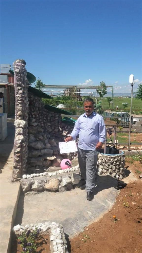 Salih Yosuf in his garden, standing in front of the water feature he built