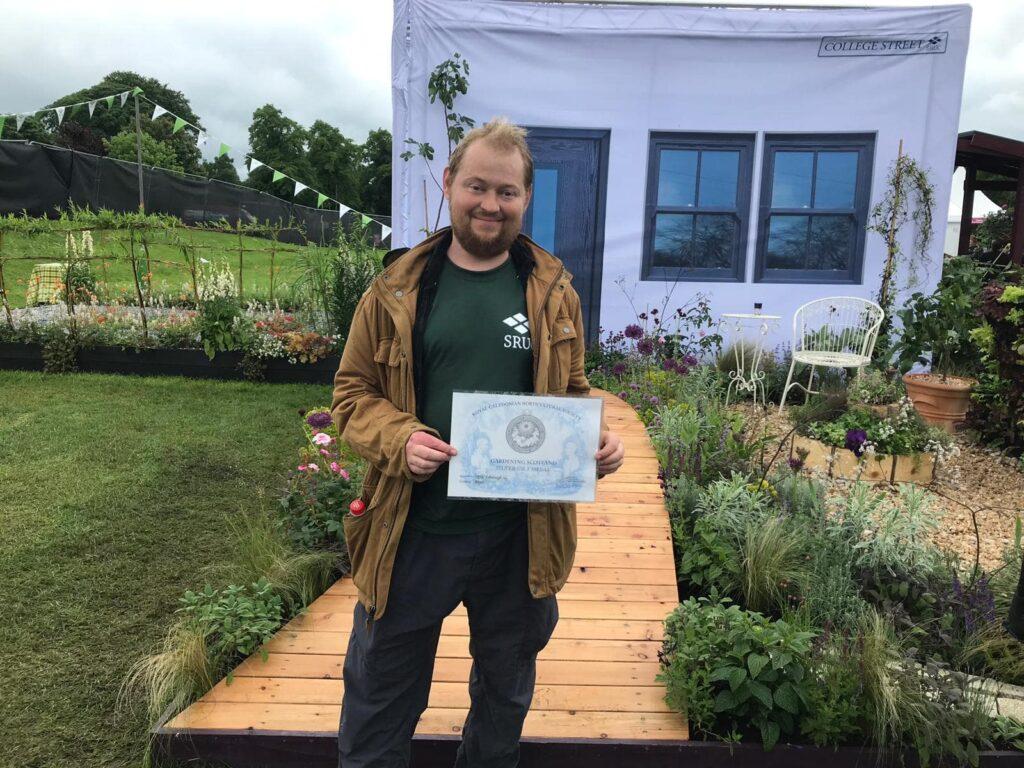 John Thoumire standing his show garden called 'Bayet' at Gardening Scotland - holding certificate